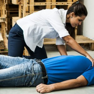 worker giving first aid to another worker